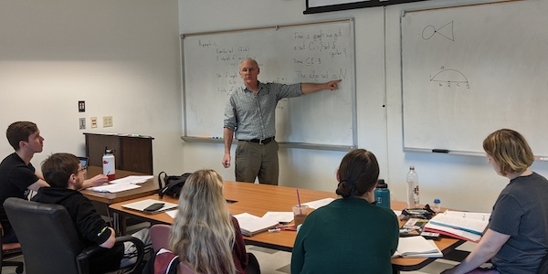 Micheal O'Sullivan at working at the whiteboard in front of a groups of graduate students